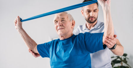Older gentleman working with exercise bands with a physical therapist.